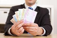 Manager im Büro hält Geldscheine