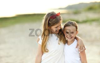 Happy little girls enjoying summer day on beach