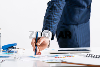 Businesswoman standing near office desk with pen