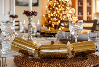 Traditional family Christmas lunch table set with crackers with tree in background