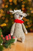 The cute knitted toy deer on the Christmas tree background