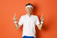 Portrait of healthy, handsome middle-aged male athlete, doing sports and feeling happy, pointing fingers up at logo, standing in activewear over orange background