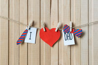 Fathers day concept. Message with paper hearts, tie and bow-tie hanging with pins over light wooden board.