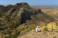 Mann sitzt auf einem Felsvorsprung und blickt über das Gheralta Bergmassiv, Tigray, Äthiopien