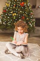 Girl writes letter to Santa near christmas tree