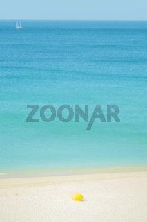 gelber sonnenschirm am strand, segelboot