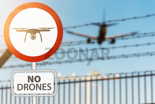drone prohobition sign against security fence and plane landing on airport
