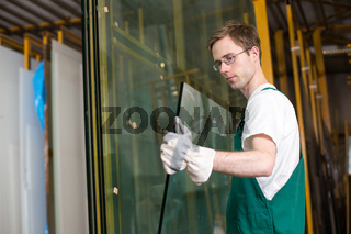 Glazier in workshop handling glass