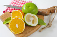 Green grapefruits and halved orange