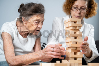 Senior woman playing Jenga, build tower of blocks. Elderly doctor in white lab coat, supporting senior patient, developing logic, fine motor skills, Alzheimer disease at home with old lonely female
