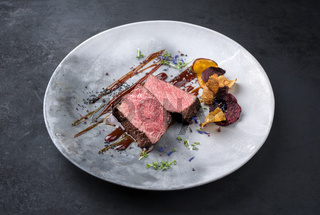 Barbecue dry aged wagyu roast beef natural sliced and offered with vegetable chips and herbs as closeup on a modern design plate with copy space