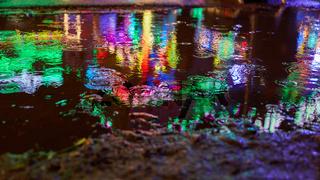 Pfütze nachts bei Regen auf Jahrmarkt oder Kirmes