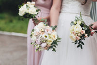 Bride in white dress holds wedding bouquet with bridesmaids. Blurred background