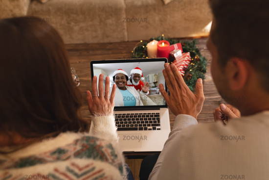 Rear view of couple waving while having a videocall with santa claus and senior woman in santa hat o