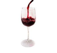 Red wine pours into a tall glass