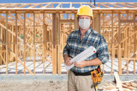 Male Contractor In Hard Hat Wearing Medical Face Mask During Coronavirus Pandemic At Construction Site