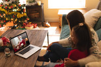 Woman and daughter sitting on the couch having a videocall with santa claus wearing face mask on lap
