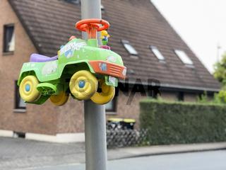 Bobby Car an einer Straßenlaterne warnt Autofahrer