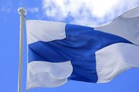 Flag of Finland Against Blue Sky and White Clouds