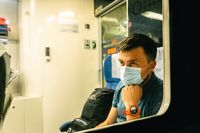 Sad man wears protective mask in train to protect the respiratory system from coronavirus infection, covid-19. Preventive measure. New normal. Travel safely on railway public transport