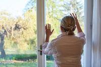 Seniorin am Fenster zu Hause während Lockdown Quarantäne blickt nach draußen