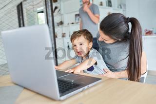 Kleinkind spielt am Laptop Computer im Wohnzimmer