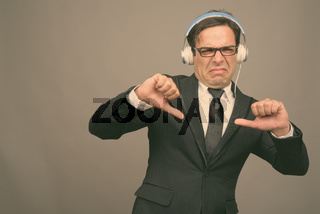 Handsome Persian businessman listening to music against gray background