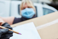 Lieferdienst Paketbotin mit Mundschutz bittet um Unterschrift