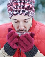 Mann im kalten Winter trinkt Tee