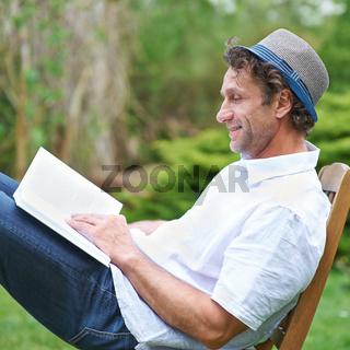 Mann liest Buch im Garten