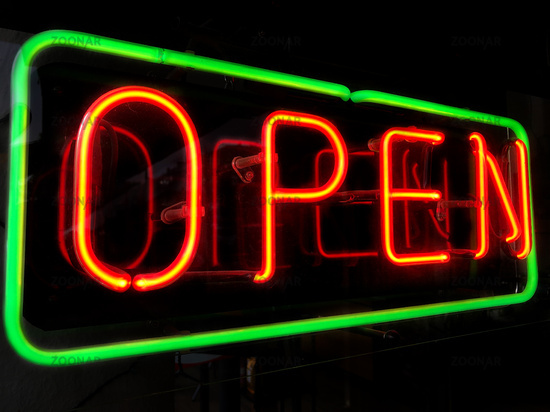 open neon sign in shop window at night