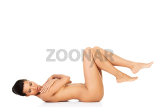 Naked attractive woman lying on her back with legs up.