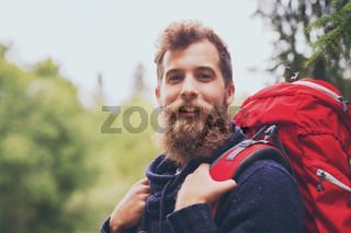smiling man with beard and backpack hiking