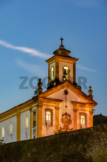 Old and historic 18th century church with its facade illuminated at sunset
