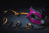 Carnival mask with golden ribbon on black background