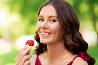 happy woman eating strawberry at summer park