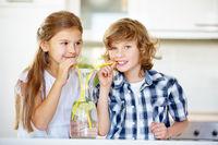 Kinder trinken Wasser mit Strohhalm