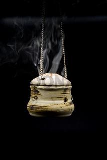 bowl of incense hanging smoke on black background