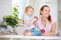 Familie mit Mutter und Tochter beim Apfel essen