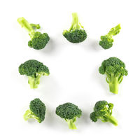 Broccoli florets, shot from above on a white background, forming a square frame with copy space