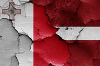 flags of Malta and Latvia painted on cracked wall