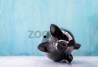 Schwarzes Sparschwein liegt auf der Seite