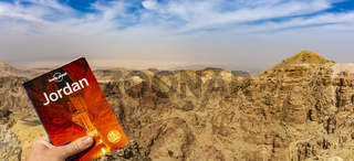 Lonely Planet travel guide against dramatic Jordan mountains and sky to promote travel and tourism to Jordan.