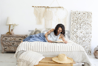 Attractive pregnant woman lying on bed reading book in bedroom