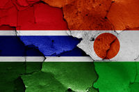 flags of Gambia and Niger painted on cracked wall