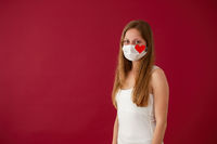 Solitary young Caucasian woman smiling under white face mask with red heart sign