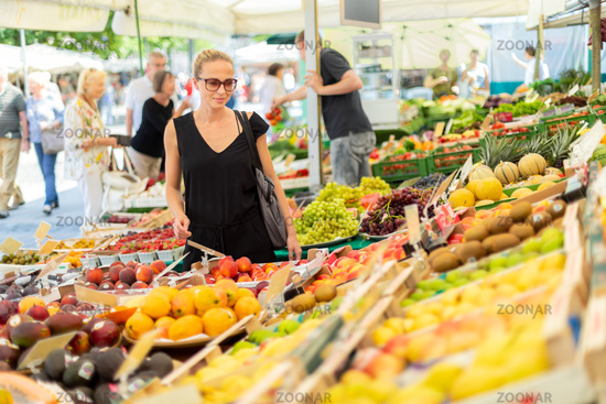 Woman buying fruits and vegetables at local food market. Market stall with variety of organic vegetable