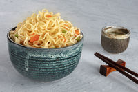 Instant noodles bowl with carrot and scallions, with chopsticks and sake