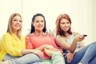 three smiling teenage girl watching tv at home
