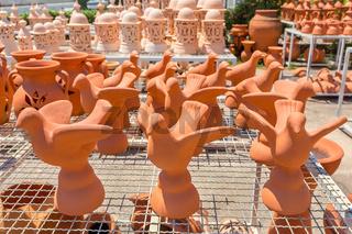 Many orange birds of clay  outside at pottery
